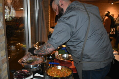 Chef standing over pans of food